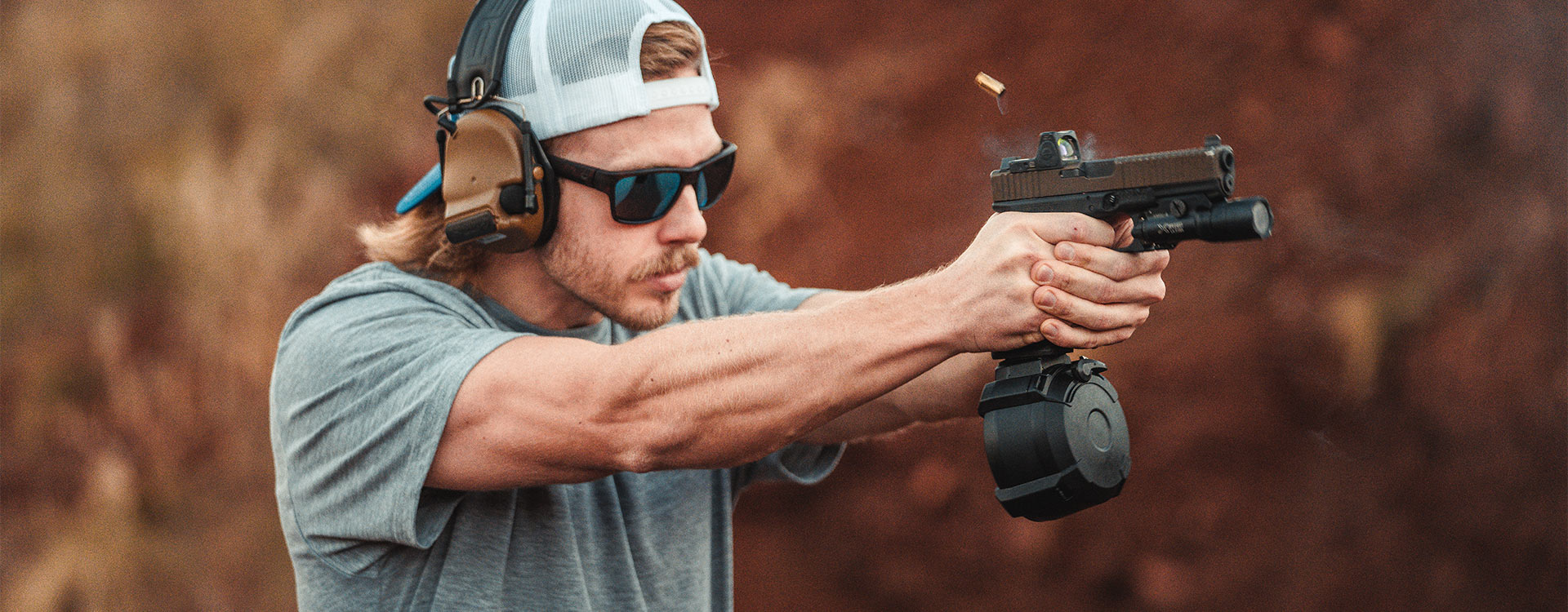 Shooter in Magpul Eyewear firing custom Glock with Magpul PMAG D-50 GL9 drum