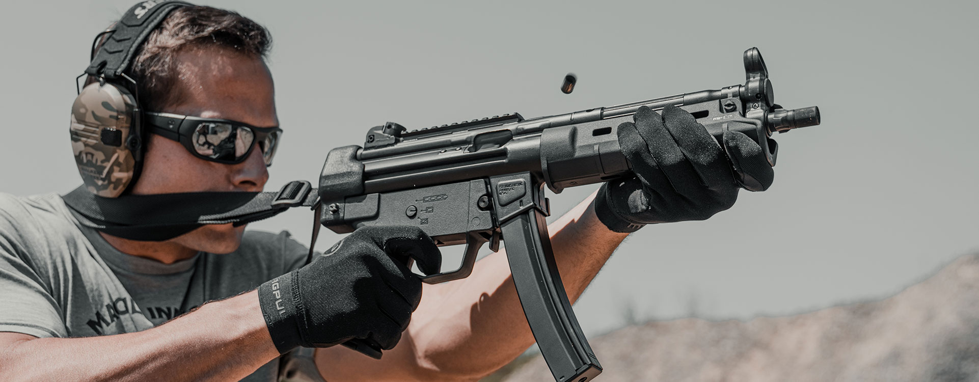 SL Hand Guard MP5 on a HK pistol with SL Grip Module, ESK, and Magpul Sling being fired by a man with Magpul glasses