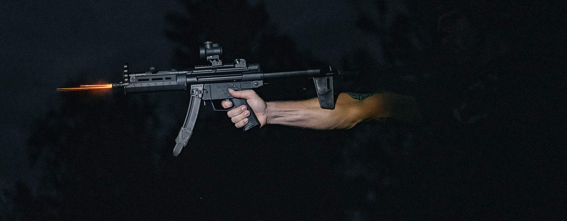 MP5 with Magpul BSL HK94/MP5 Arm Brace being fired with one hand in a dark room, with sparks shooting out barrel
