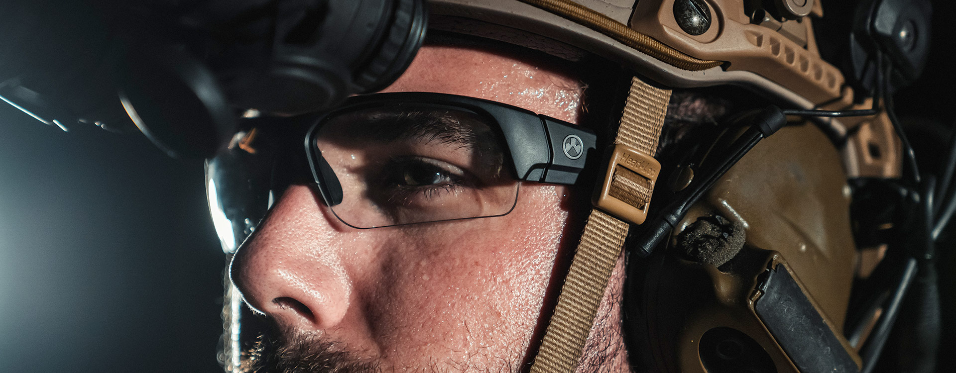 Lit nighttime image of Magpul Helix Eyewear, Black Frame, Clear Lens on a man with ear-pro, helmet, and night vision