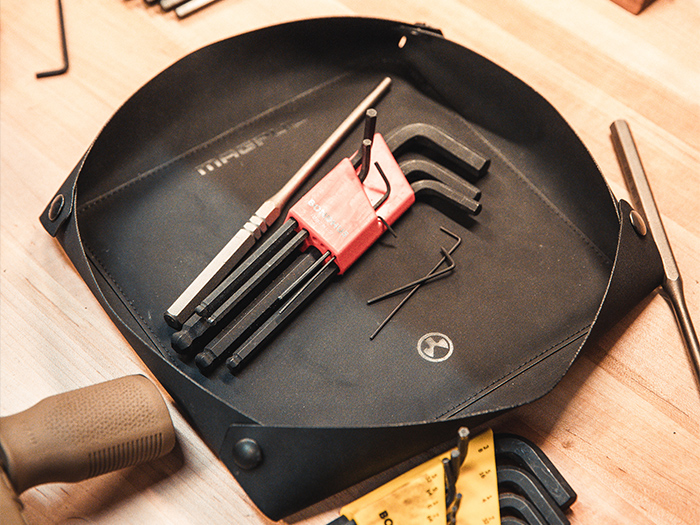 Large Magpul DAKA Magnetic Field Tray filled with tools on workbench next to rifle with MOE MVG