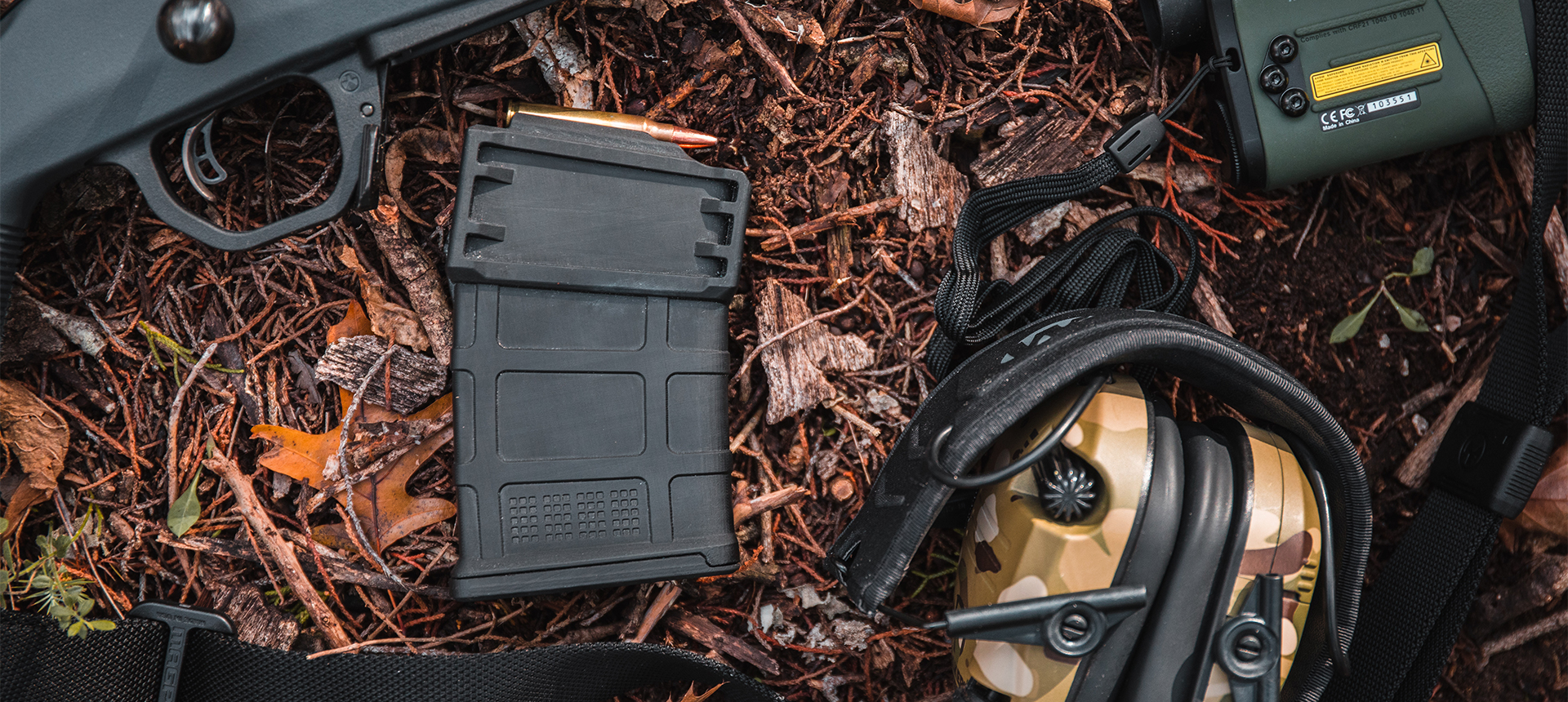 Loaded Magpul PMAG 10 5.56 AC on the ground surrounded by a variety of typical shooting accessories