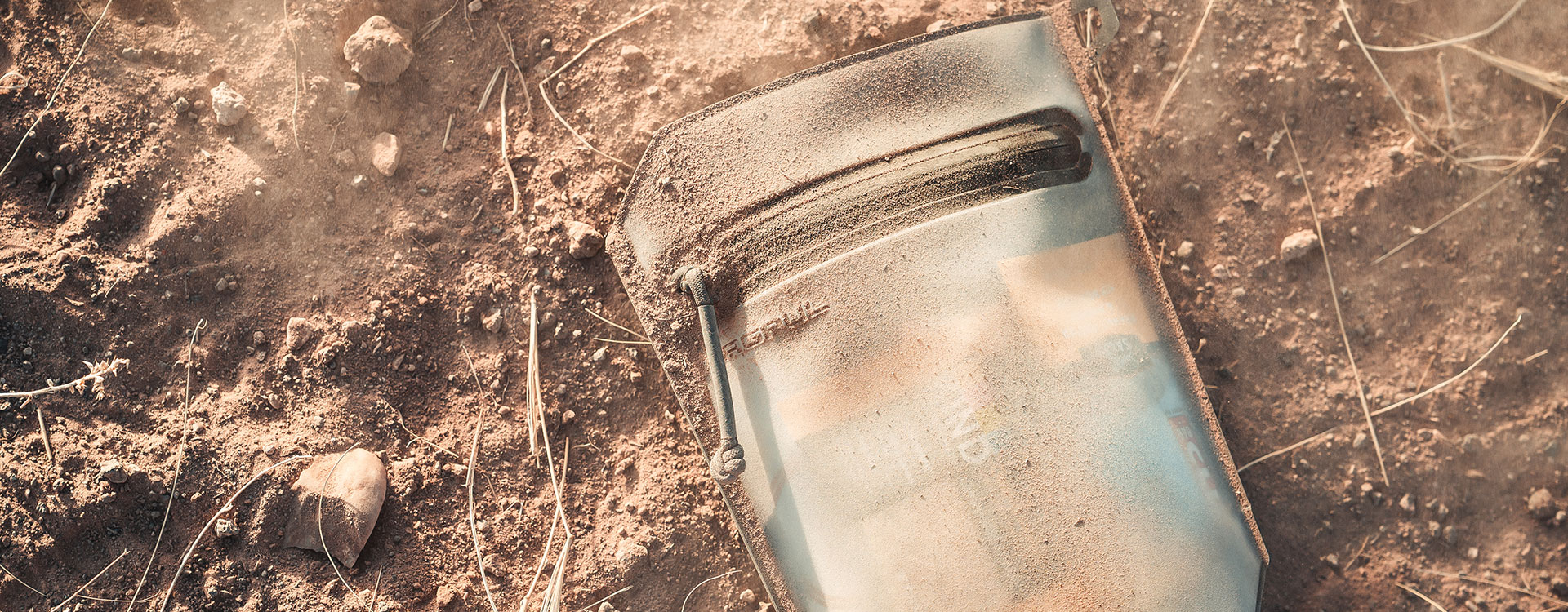 Magpul DAKA Volume Pouch on ground covered in dirt, full of misc camping items