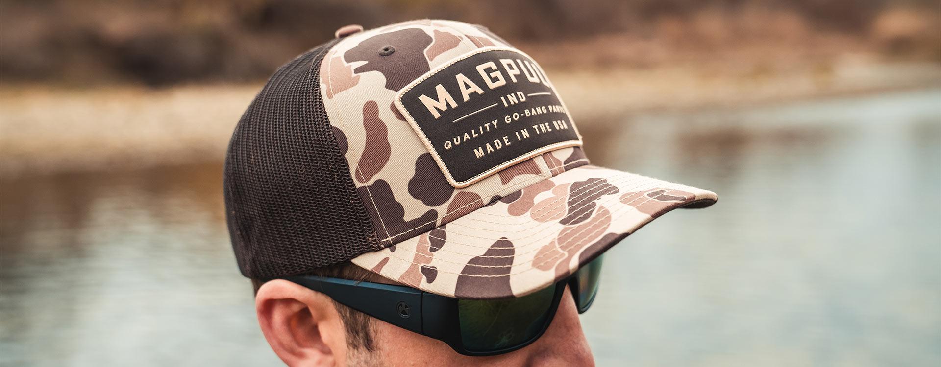 Magpul Go Bang Trucker in Raider Camo on man wearing Magpul Eyewear outdoors near lake