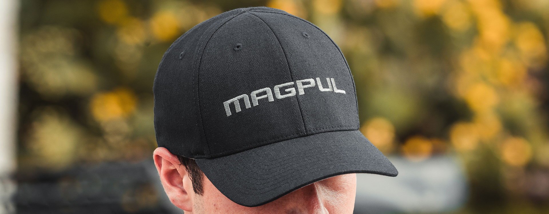 Hero image of Black Magpul Wordmark Stretch Fit Hat being worn by a man