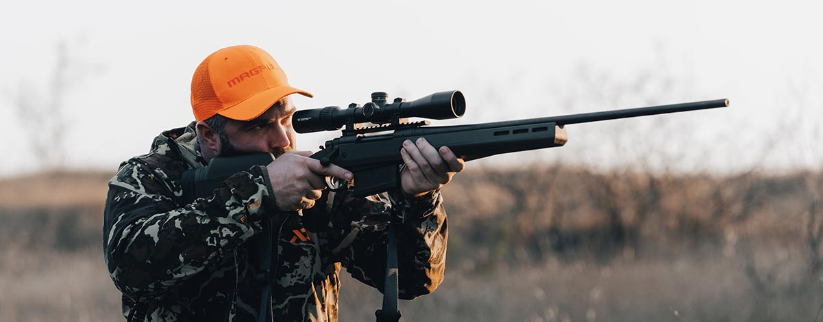 Magpul Wordmark Blaze Orange Trucker on man with camo shouldering a scoped rifle with Magpul Hunter Stock.