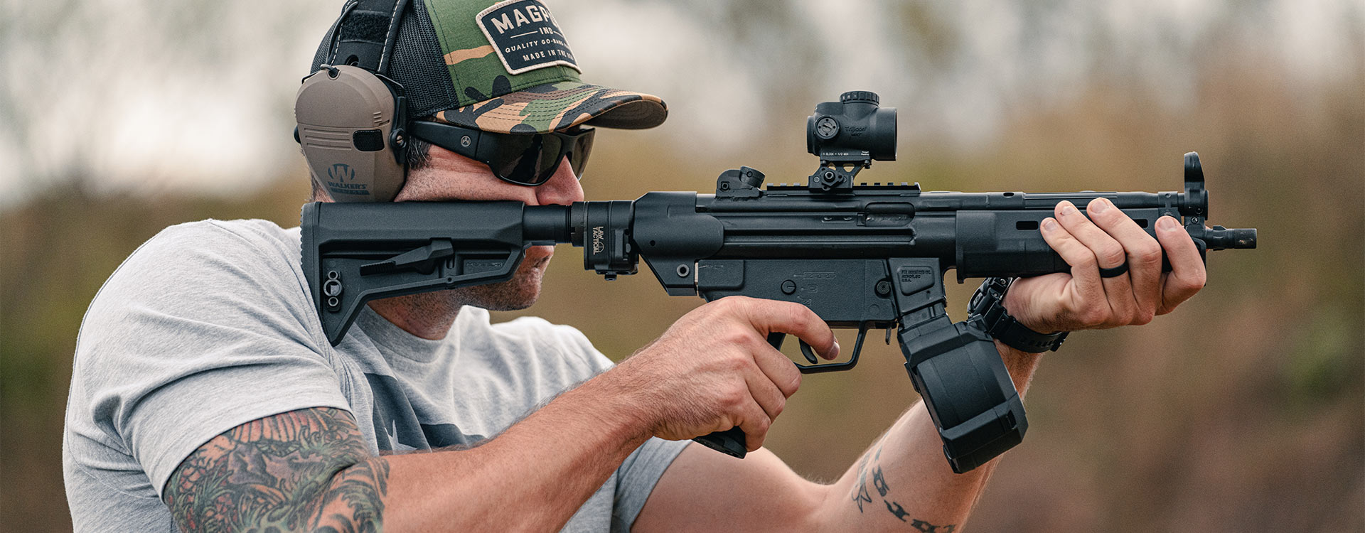 Magpul Rift Eyewear - Black Frame, Gray Lens on a shooter firing MP5 with Magpul D-50 Drum and MOE SL-K Stock