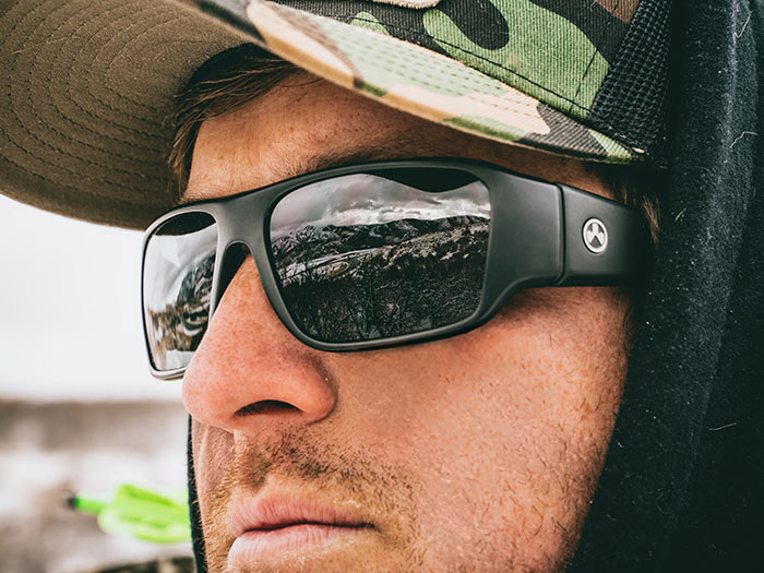Magpul Rift Eyewear - Black Frame, Gray Lens on a man with black hoodie and Magpul Camo Trucker Hat