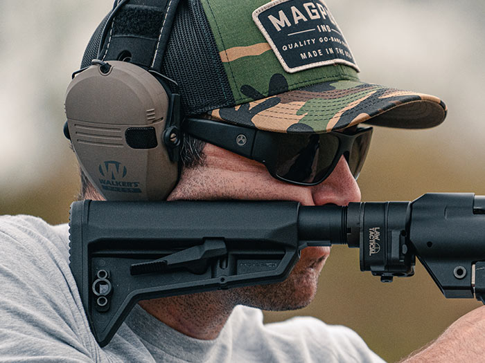 Magpul Rift Eyewear - Black Frame, Gray Lens on a man in Magpul Camo Trucker Hat shooting a gun with SL-K Stock