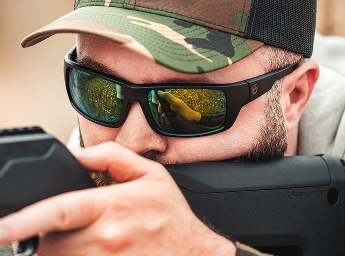 Magpul Apex Eyewear, Polarized - Black Frame, High Contrast Violet Lens/Green Mirror on man in ballcap firing rifle