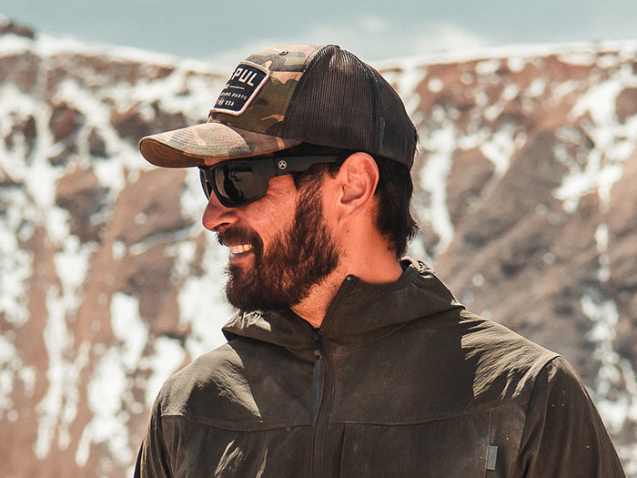 Magpul Ascent Eyewear, Polarized - Black Frame, Gray Green Lens on bearded man outdoors with Magpul Trucker Hat