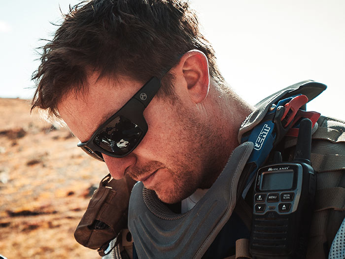 Magpul Ascent Eyewear - Black Frame, Gray Lens on man in offroad clothing outdoors taking a rest after a ride