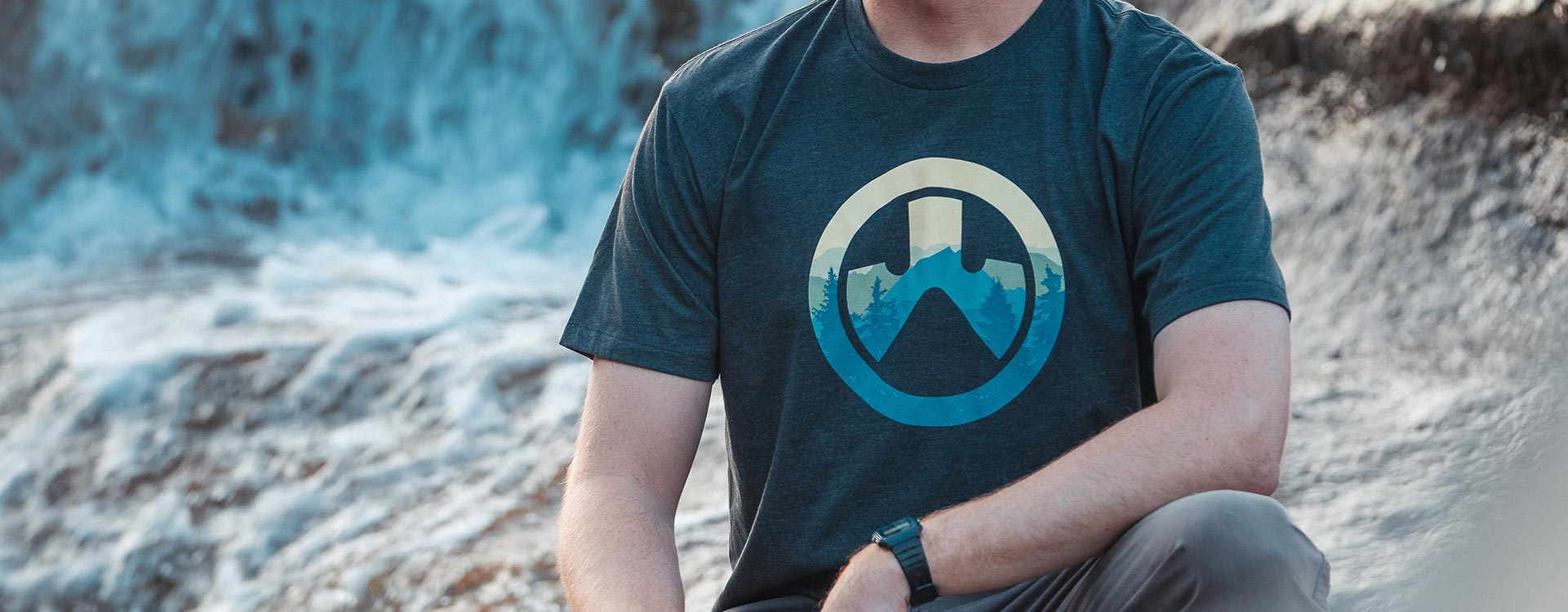 Magpul Cascade Icon Logo CVC T-Shirt on man crouching outside with rocky background