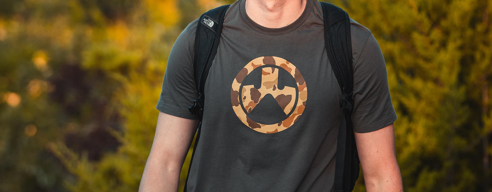 Magpul Raider Camo Icon Cotton T-Shirt worn by a man wearing a backpack outdoors