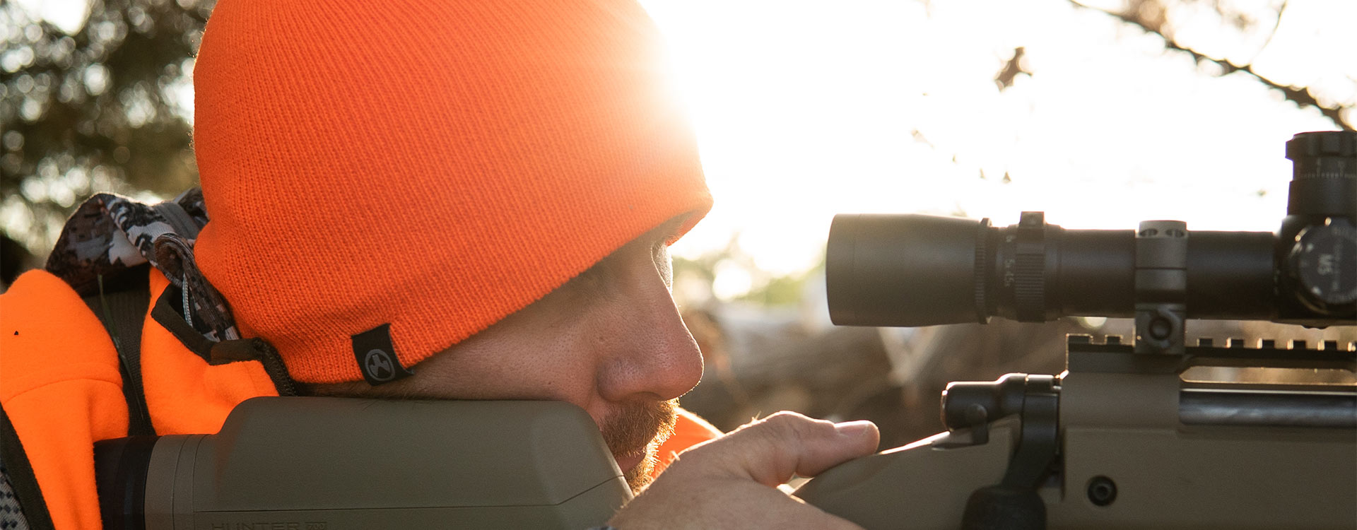 Orange Magpul Beanie with black, logoed tag worn by a hunter who's aiming a rifle through a scope