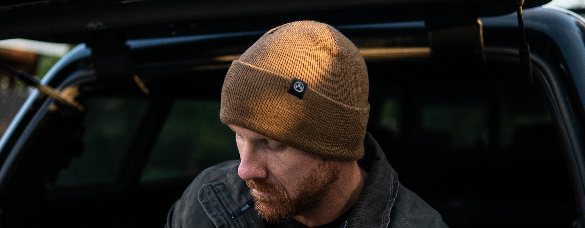 3.Brown Magpul Watch Cap with black, logoed tag over edge of cuff worn by bearded man sitting in back of hatchback looking down