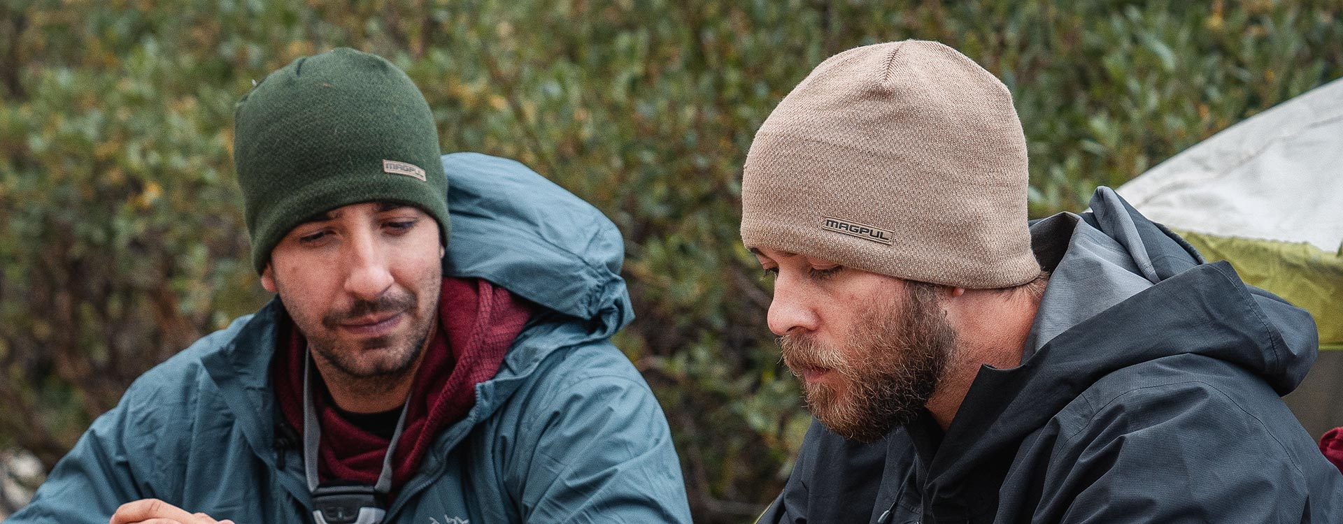 Green and Brown Magpul Tundra Beanies worn by two jacketed men camping outdoors with a tent in the background