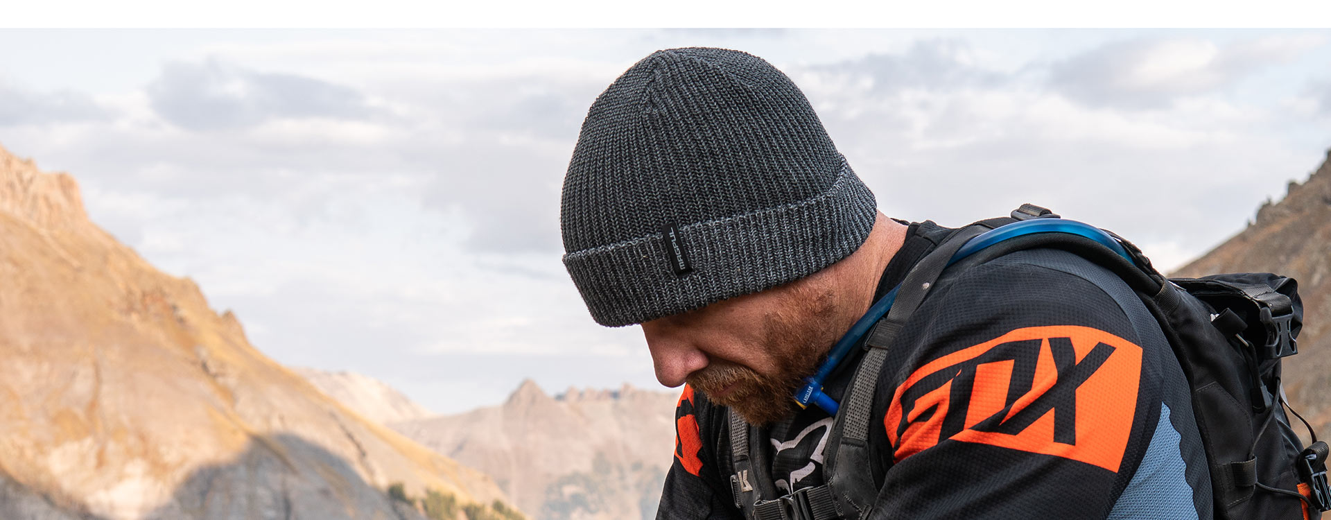 Charcoal Heather Magpul Merino Watch Cap on bearded man in technical gear taking rest at the top of a mountain