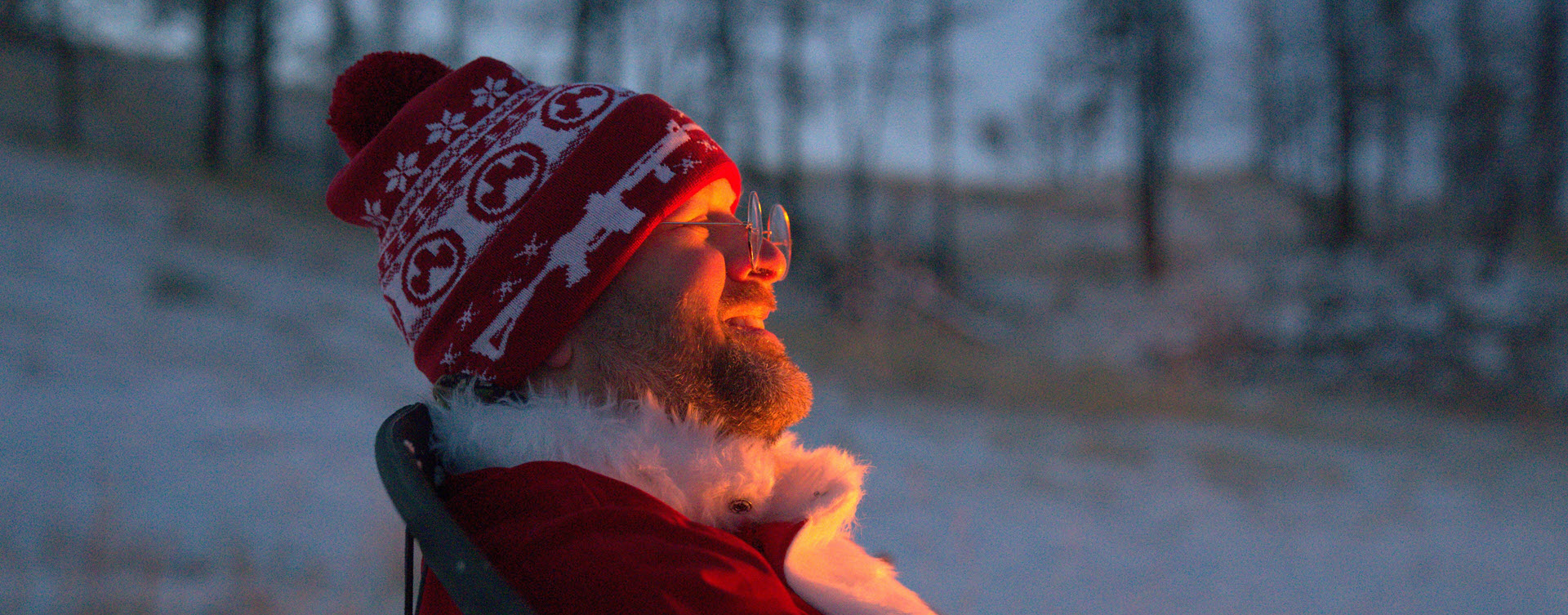 Magpul Ugly Christmas Beanie on man in Santa costume with glasses sitting outdoors in the snow by a fire