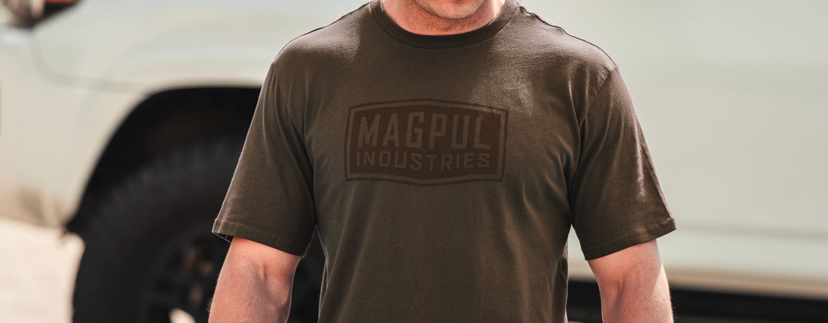 Brown Magpul Industries Fine Cotton T-Shirt worn by an unidentifiable man with a white truck in the background