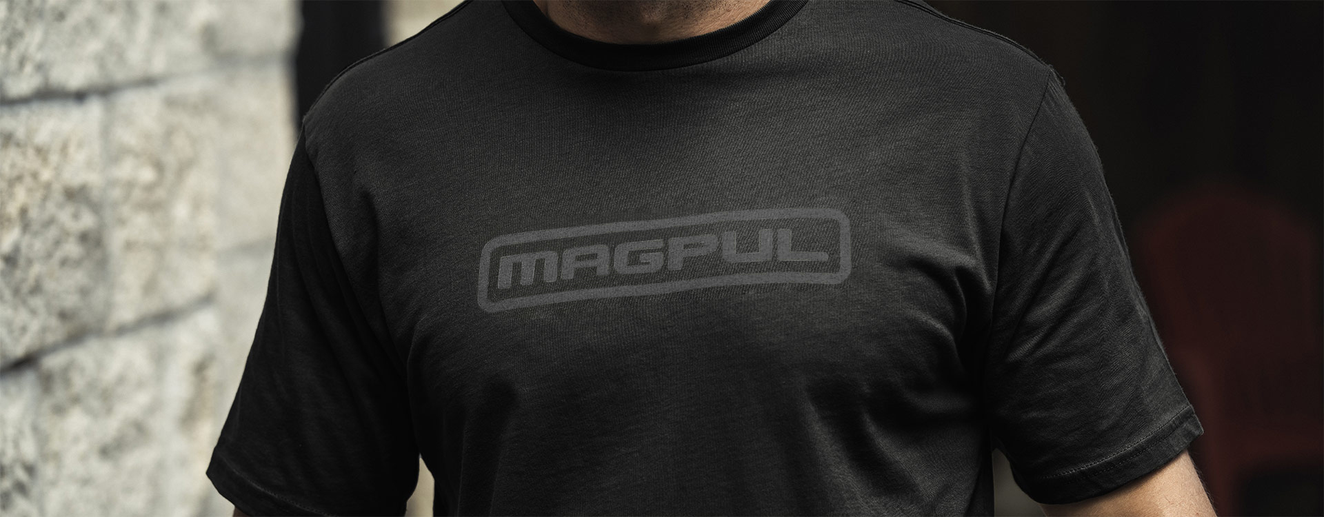 Magpul Wordmark Logo T-Shirt worn by an unidentifiable man with a blurred stone wall in background