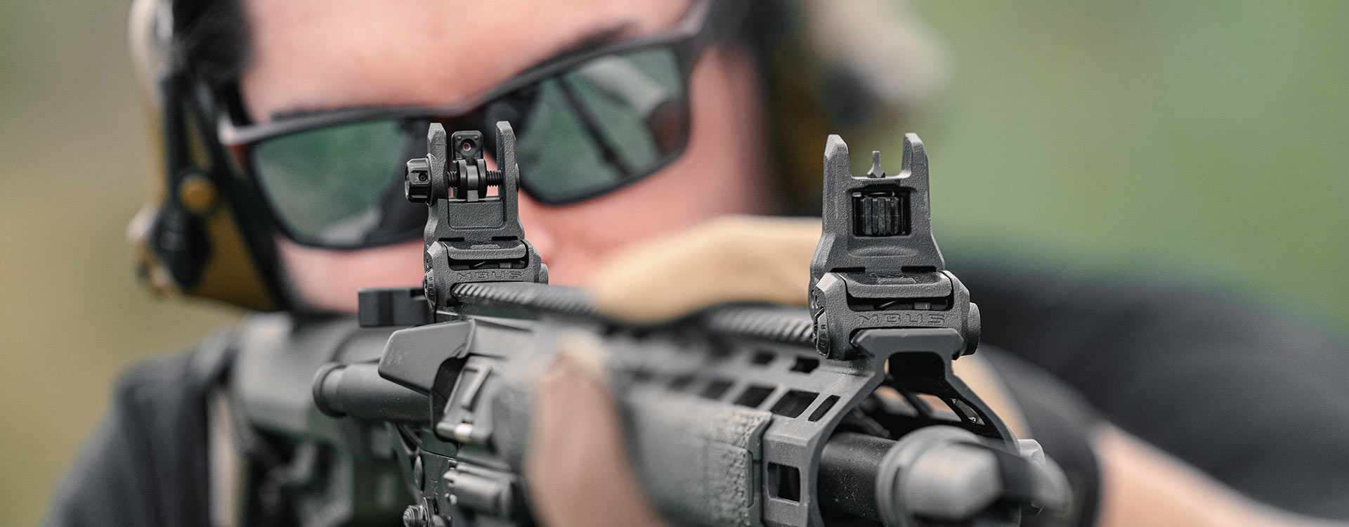 Shooter in Magpul Eyewear aiming with a set of MBUS 3 Sights on an AR15