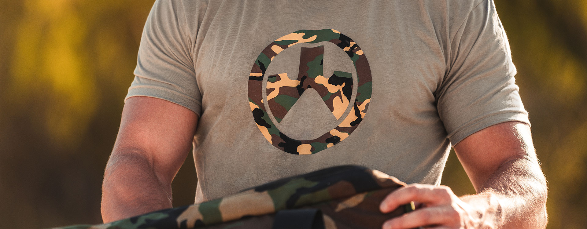 Man handling camo pack and wearing Stone Gray Magpul Woodland Camo Icon CVC T-Shirt with indistinct outdoor background