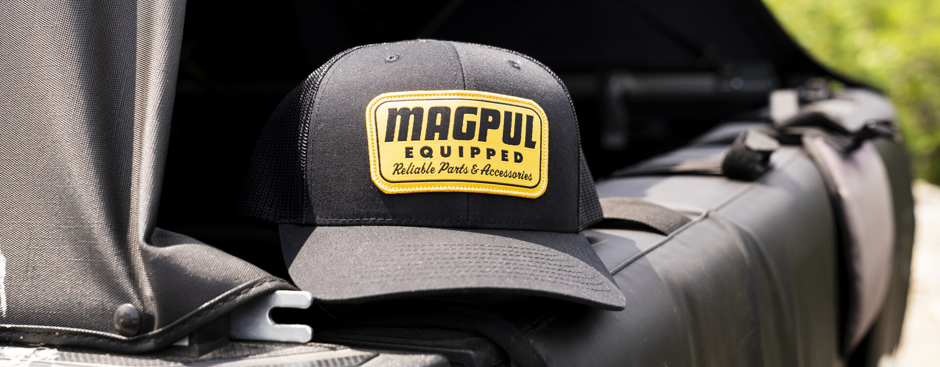 Magpul Equipped Trucker hat in Black with large yellow Magpul Equipped patch on crown sitting on the back of an open tailgate