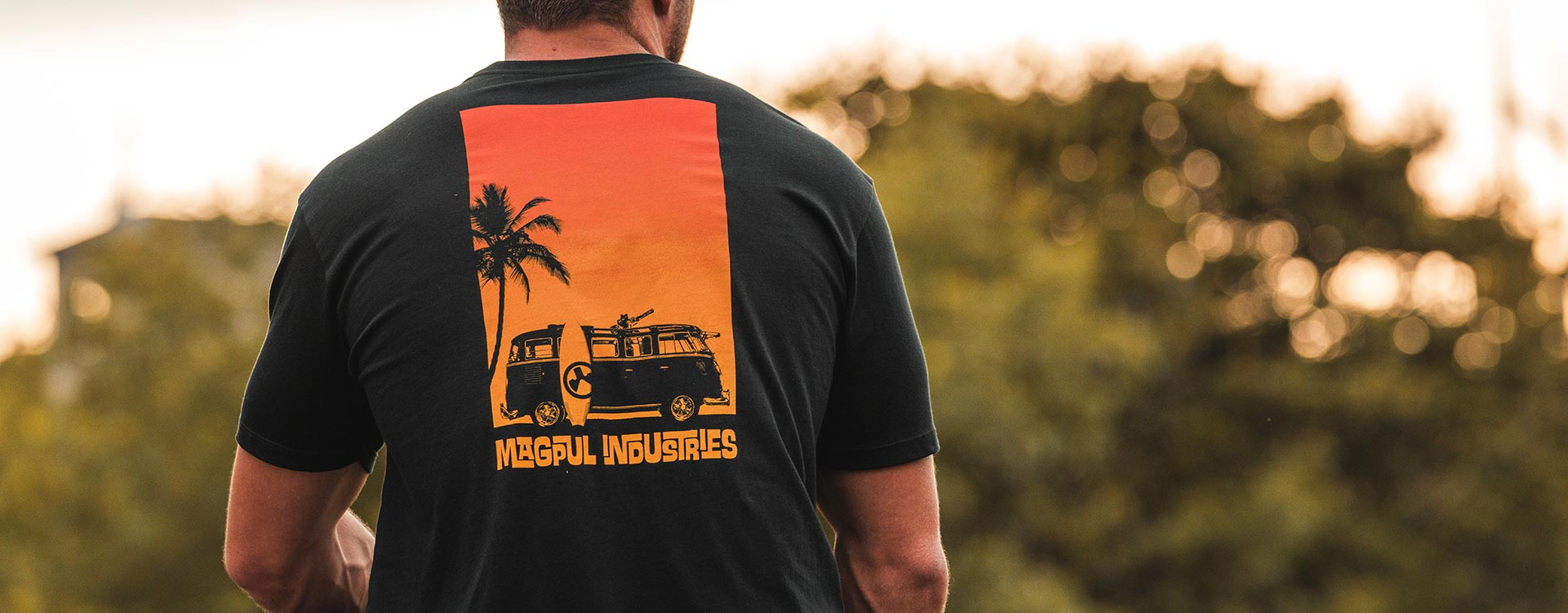 Back of Magpul Sun's Out Cotton T-Shirt back print of Microbus with minigun on a sitting man outdoors