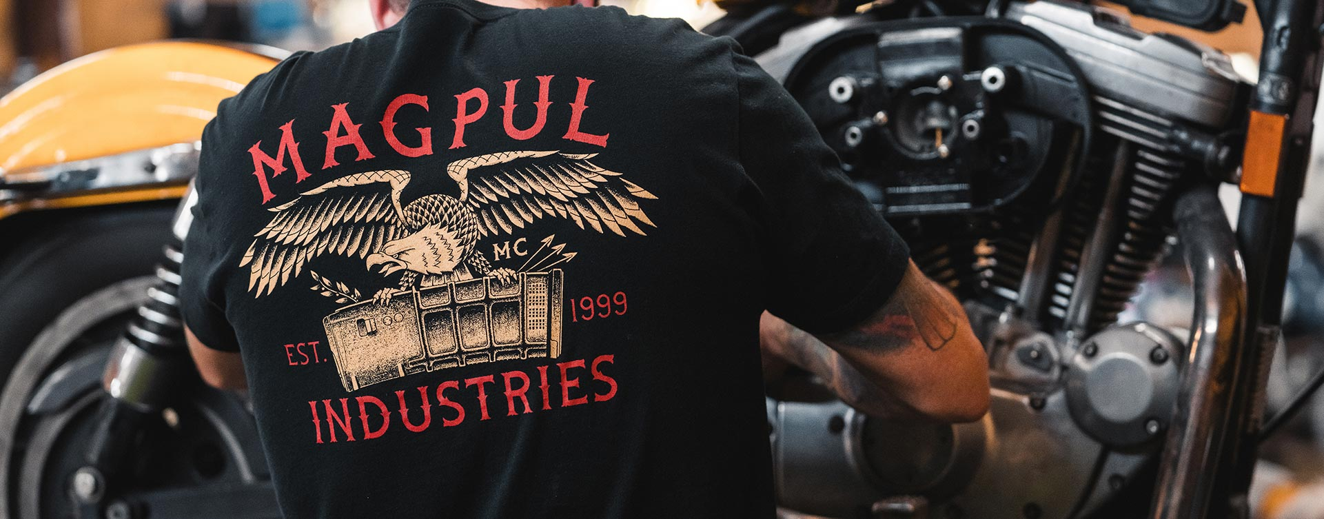 Back of Magpul Magazine Club Cotton T-Shirt on man working on a motorcycle in the shop