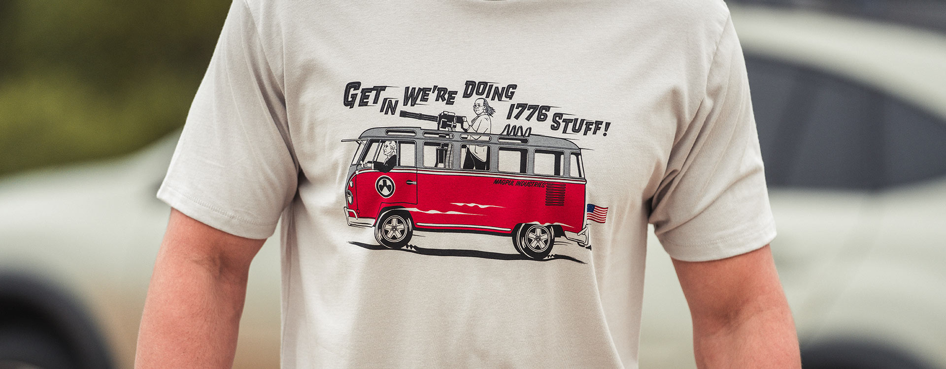 Magpul Freedom Bus Cotton T-Shirt with front graphic worn by nondescript man with white sports car in background