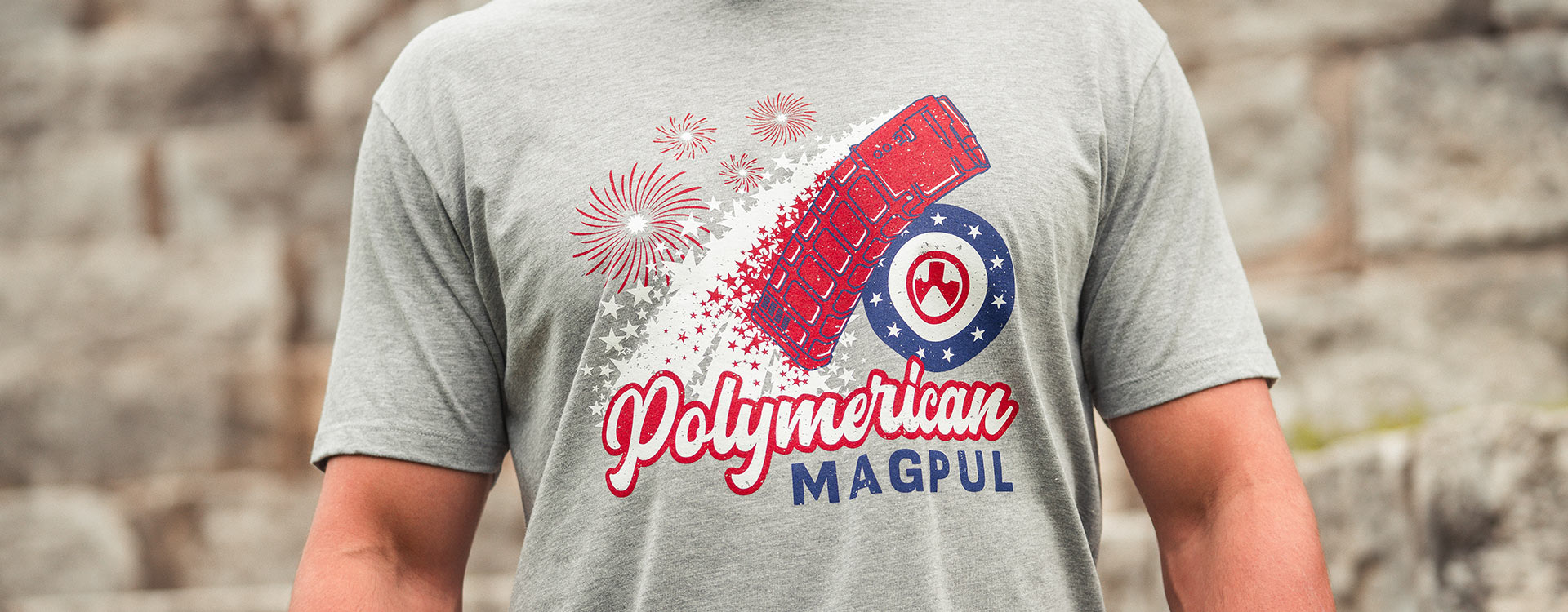 Magpul Polymerican Blend T-Shirt with red, white and blue graphic of fireworks inspired PMAG worn by nondescript man outdoors