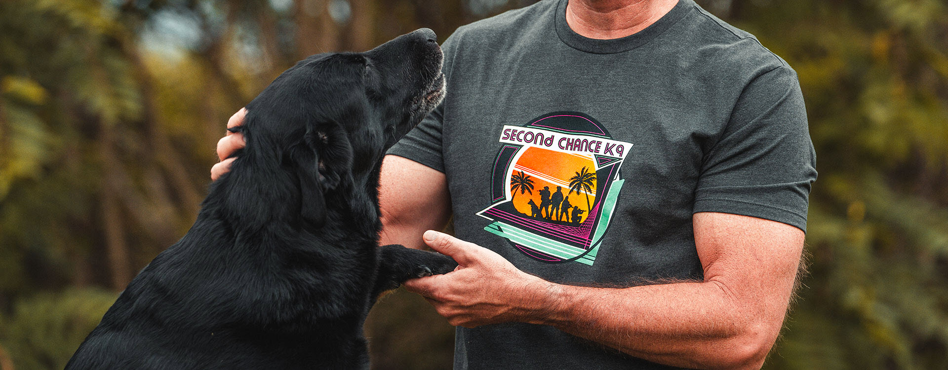 Magpul Second Chance K9 T-Shirt with 80's inspired graphic on chest of K9 and handlers worn by man outdoors with Black Lab